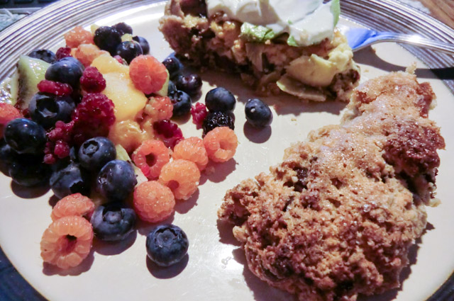 A plate with three main portions: berries including blueberries, raspberries (golden, red and black), kiwi and peaches;