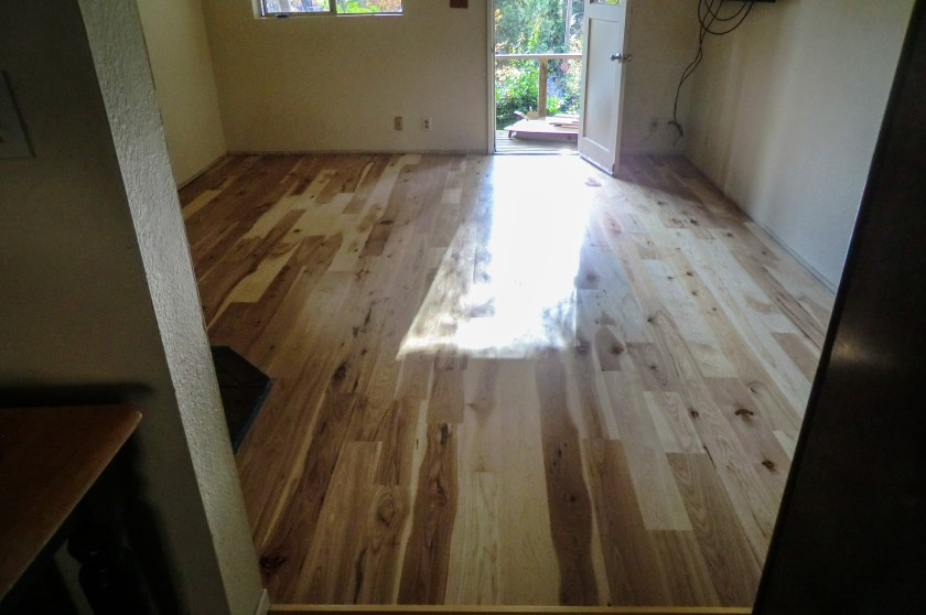 a new, hardwood plank hickory floor in a living room