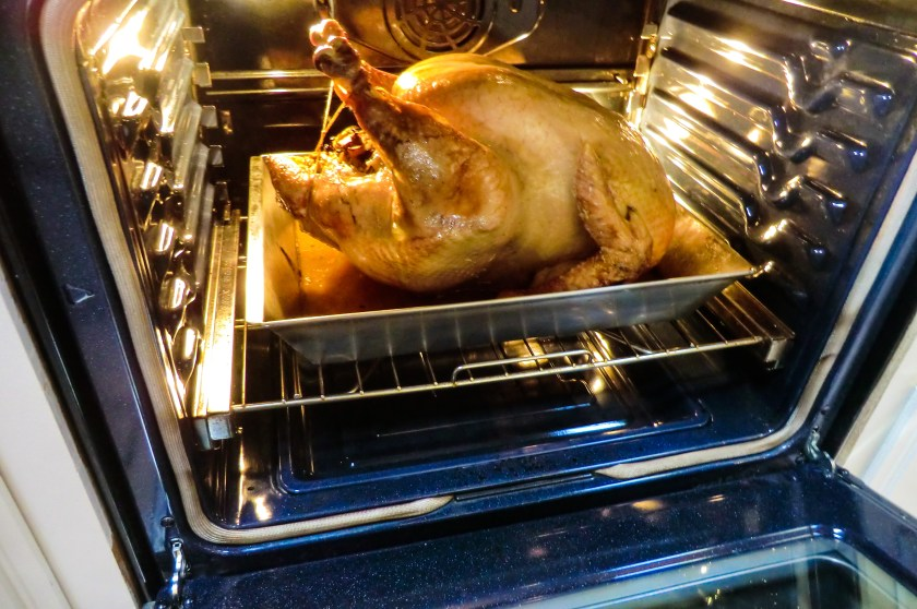 A roasting turkey in a pan in an oven