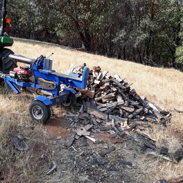 a wood splitter and stack of wood