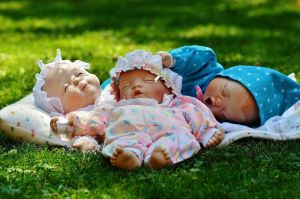 3 sleeping dolls laying on a blanket on the grass