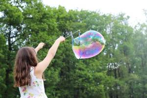 a young girl waving a bubble wand