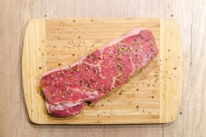 beef with spices on a wood cutting board