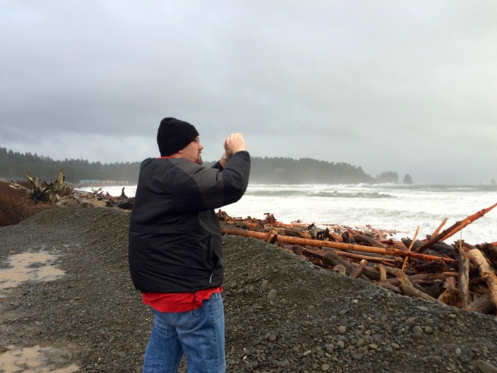 Jason braces himself against the wind while taking a photo of First Beach in Olympic National Park