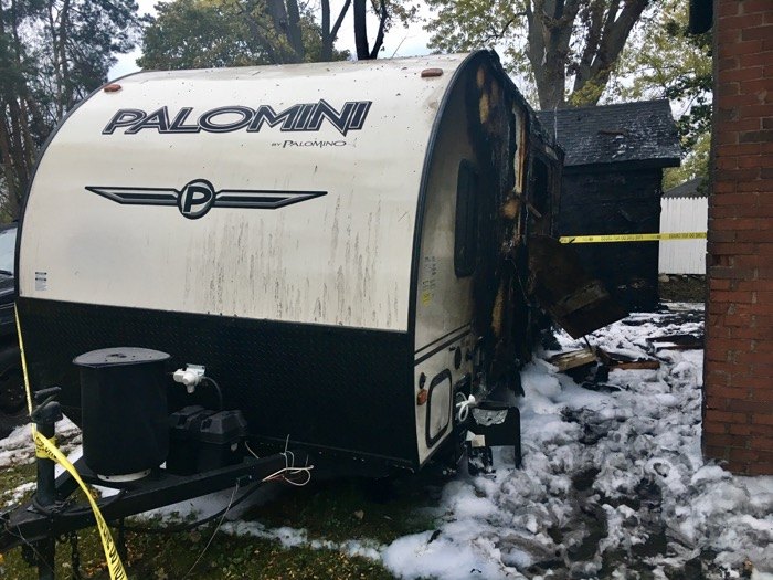 Front view of camper, fire damage visible along the side