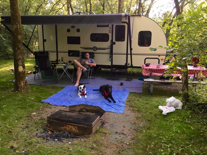 Jason, Naya, and Bailey relax outside the camper at Rock Cut State Park