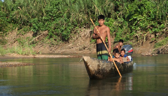 A young Huaorani man guides his family up the Shiripuno and past our canoe. A proud, striking figure.