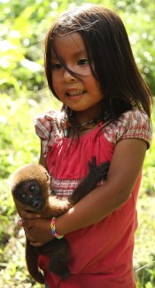 A young Huaorani girl cradles her precious pet monkey.