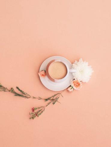 filiżanka kawy z kwiatami obok
