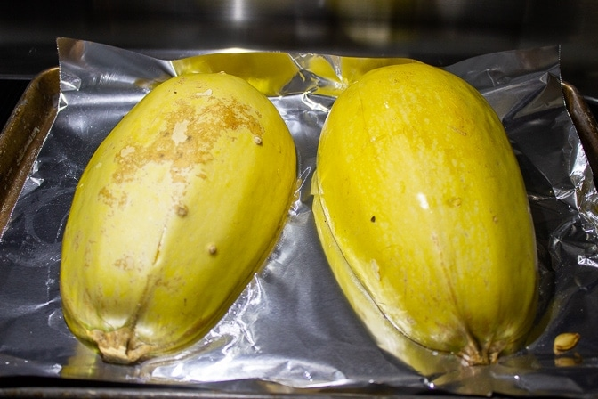 Spaghetti Squash two halves face down on pan ready to bake