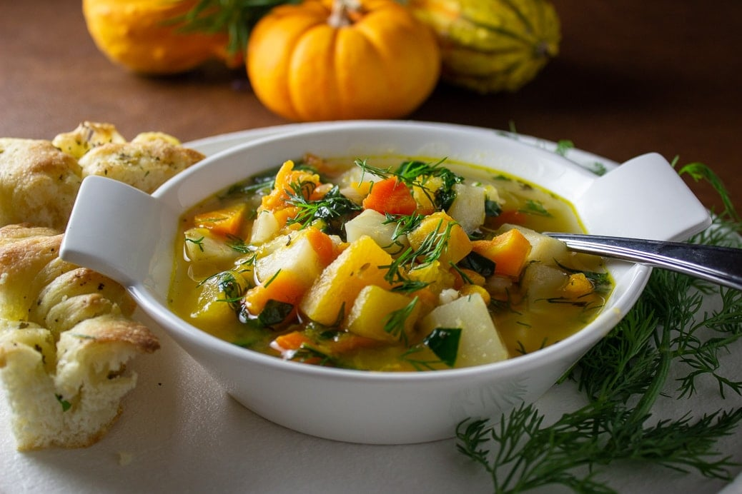 bowl of root vegetable and barley soup with gourds in background