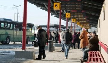 Cilvēki Starptautiskās autoostas autobusu attiešanas vietā.
