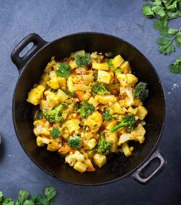 Indian Aloo Gobi dish with potato, cauliflower and spices on the textured grunge background