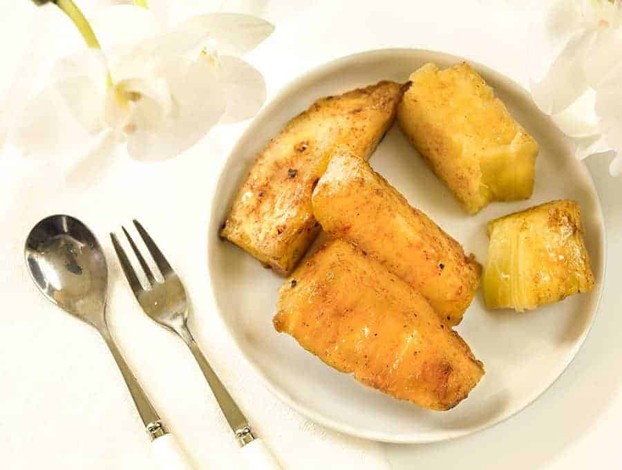 Brazilian Grilled Pineapple spears in a white plate, overhead view