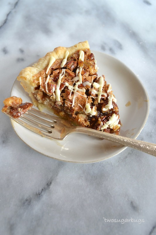 This white chocolate pecan pie is simple to prepare and sure to impress. It has a sweet and gooey center with chunky pecans and chunks of white chocolate. #twosugarbugs #pecanpie #thanksgivingpie #whitechocolate
