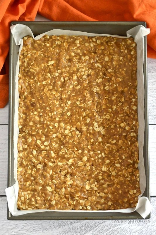 unbaked oatmeal spice layer in parchment lined baking sheet