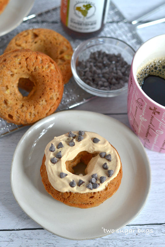 peanut butter glazed donut on a plate with plain donuts and coffee in the background