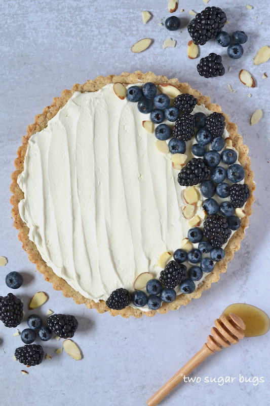 mascarpone tart with berries and a honey spoon