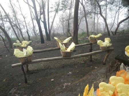 Baskets of sulphur at the rest stop half way down from the crater. In the corner are sulphur carvings sold to tourists