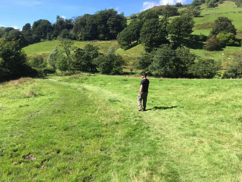 """Russell walking on the trail through a field. - """"An Introduction to England's Lake District"""" - Two Traveling Texans"""