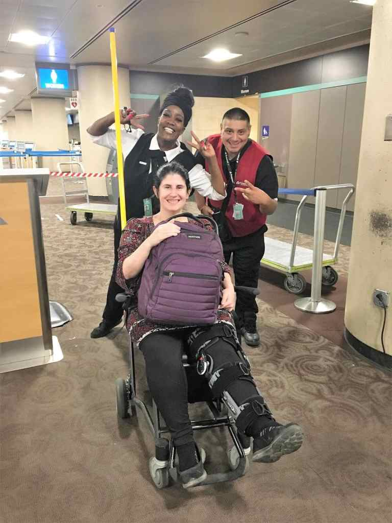 """Anisa in a wheelchair with her leg brace at the Phoenix Airport. - """"Traveling Injured: What Everyone Needs to Know"""" - Two Traveling Texans"""
