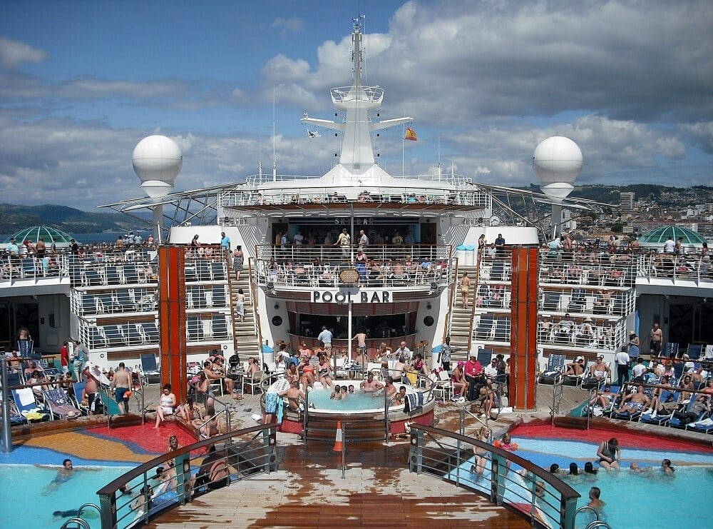 The main pool area on a cruise is the hub of activity on a day at sea - Cruise Pros and Cons- Two Traveling Texans