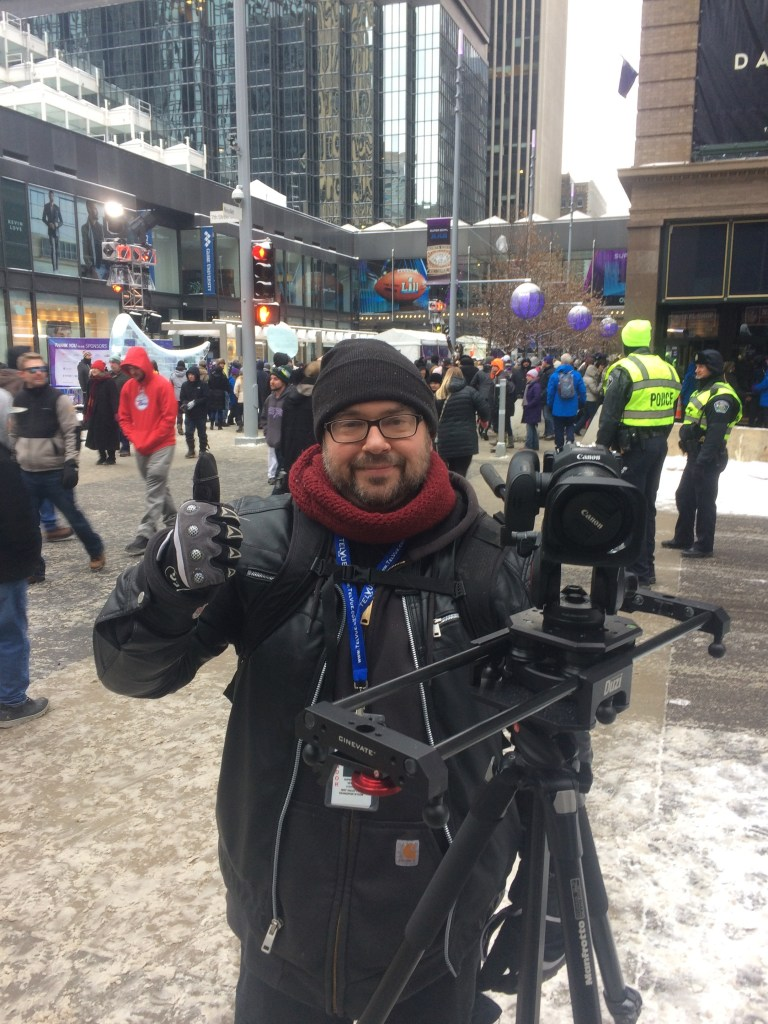 videographer standing behind camera on location at superbowl 2018