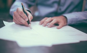 man in blue shirt writing, holding pen