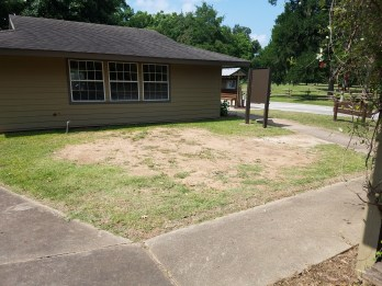 Photograph of park headquarters building with space where new pollinator garden will be installed.