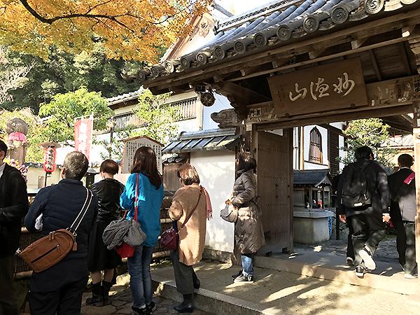 鈴虫寺の山門。山門の脇には草鞋のお地蔵さまが見えます。熱心にお祈りする人が多数。