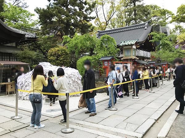「縁切り縁結び碑」にお参りする人たちの行列。若い女性だけでなく年齢・性別とも様々。