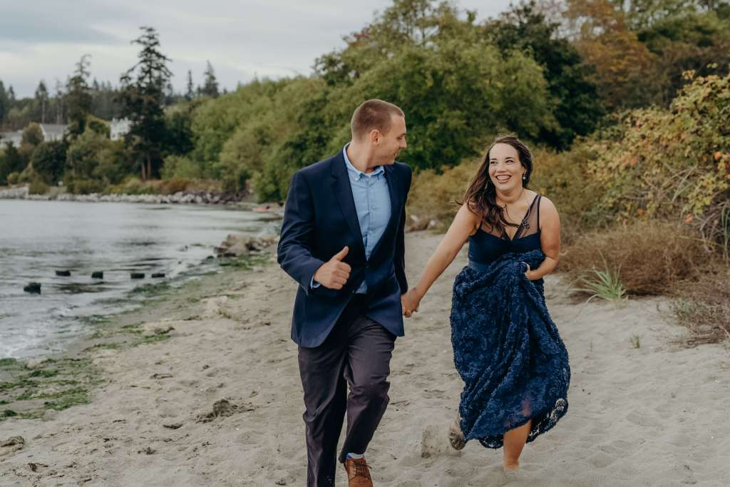 couple running on beach engagement photography