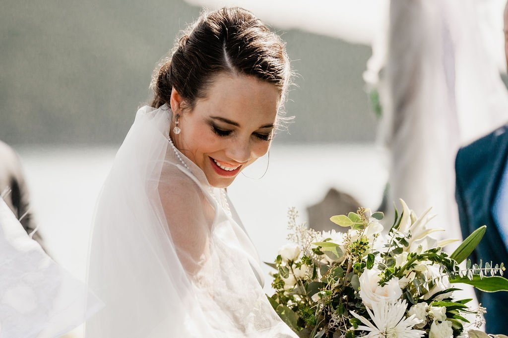 bride with veil on wedding day during ceremony with green and white bouquet at outdoor beach Pacific Northwest wedding