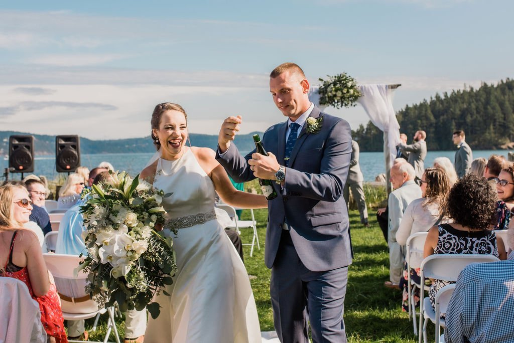 bride and groom popping champagne while walking down the aisle after Pacific Northwest outdoor wedding ceremony Seattle Anacortes
