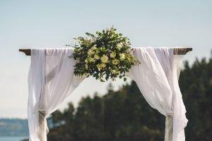 viking wedding arch, diy floral wedding arch, gauzy fabric wedding arch at. outdoor beach wedding in Pacific Northwest
