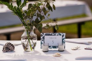 outdoor beach wedding table toppers, table numbers at navy green white wedding, fish table numbers, seashells on table, wedding matchbooks, tea lights on wedding table decor