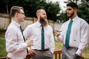 groomsmen chatting and getting ready, light gray suits, teal ties, wedding day preparations