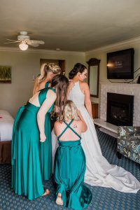 bride and bridesmaids getting ready, putting on wedding dress,