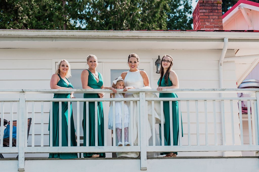 bride, bridesmaids, flower girl, on balcony, emerald green bridesmaids dresses