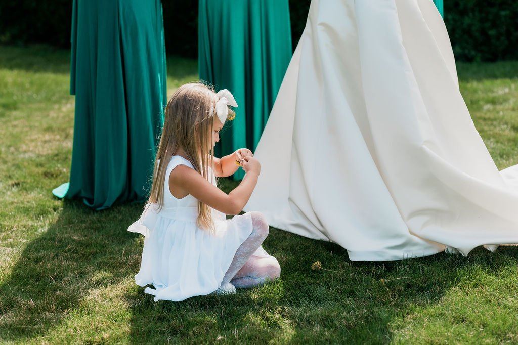 flower girl playing with flowers and brides and bridesmaids feet