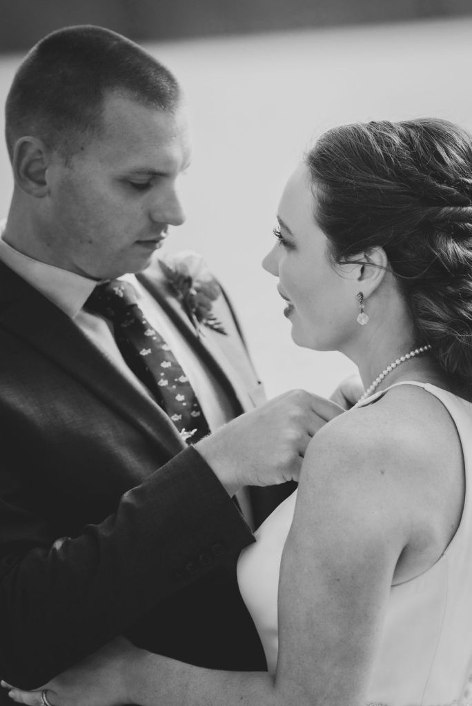 groom fixing bride's necklace, beach wedding portrait