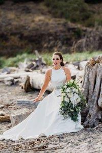 bride on beach sitting on driftwood, Pacific Northwest wedding portrait, classic bridal style
