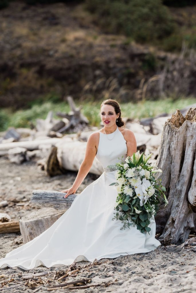 bride on beach sitting on driftwood, Pacific Northwest wedding portrait, classic bridal style
