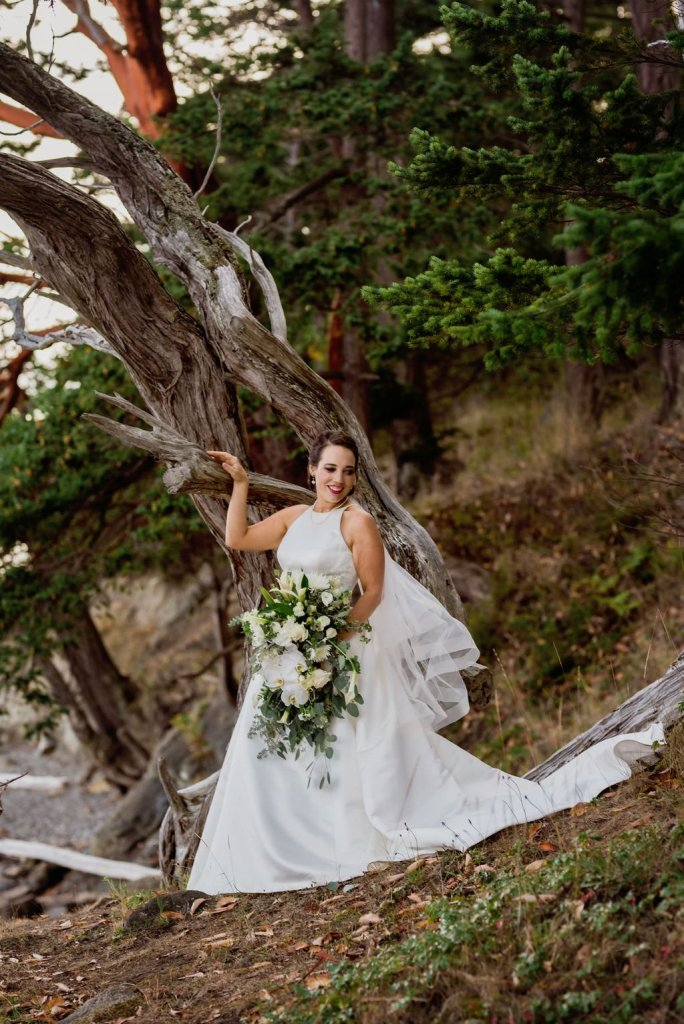 bride posing against tree, unique wedding poses, bride wedding portrait, classic bride, classic wedding dress, a line wedding dress, white and green wedding flowers