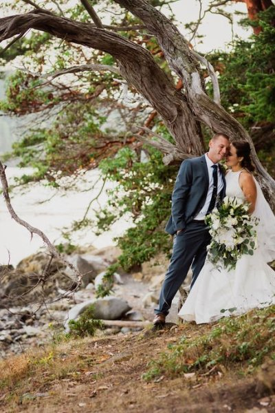 bride and groom in Washington state Pacific Northwest wedding portrait with beach and forest, bride against groom, green and white wedding flowers, dark gray suit