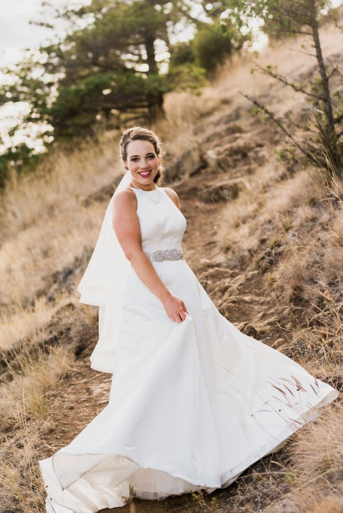 bride on mountain trail twirling in dress, classic a line wedding dress with beading and fingertip veil
