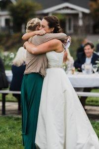 bride and maid of honor hug at wedding