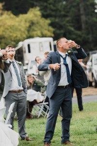 shotgunning groom at outdoor wedding, dark gray suit