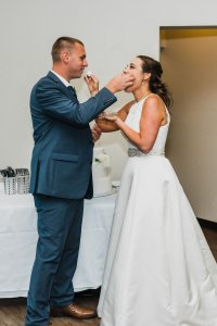 bride and groom feed each other cake, groom in gray suit brown shoes, bride in classic a line dress