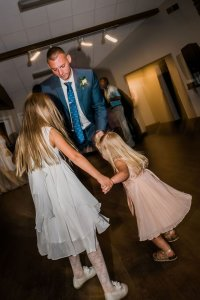groom dancing with flower girls at wedding reception